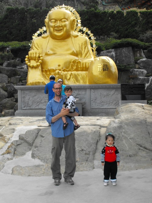Young-ju stands a safe distance from me and Ian as we all pose in front of the big gold Buddha, called Podaehwasung. If you rub his belly or nose, you will have a son.