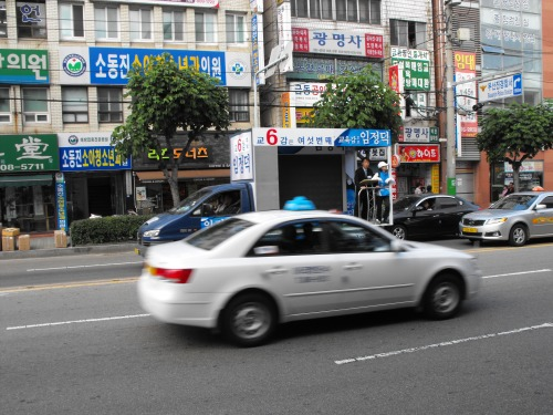 A candidate giving a drive-by speech to all the cars and pedestrians on a busy street in Busan the day before the election.